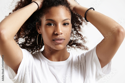 serious black woman touches her hair and watching at camera Slika na platnu