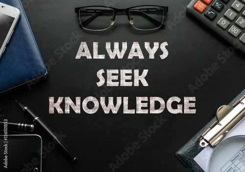 Fotografie, Obraz  Black chalkboard with business accessories (notepad, magnifying glass, fountain pen, tablet, phone, glasses and calculator) and text ALWAYS SEEK KNOWLEDGE