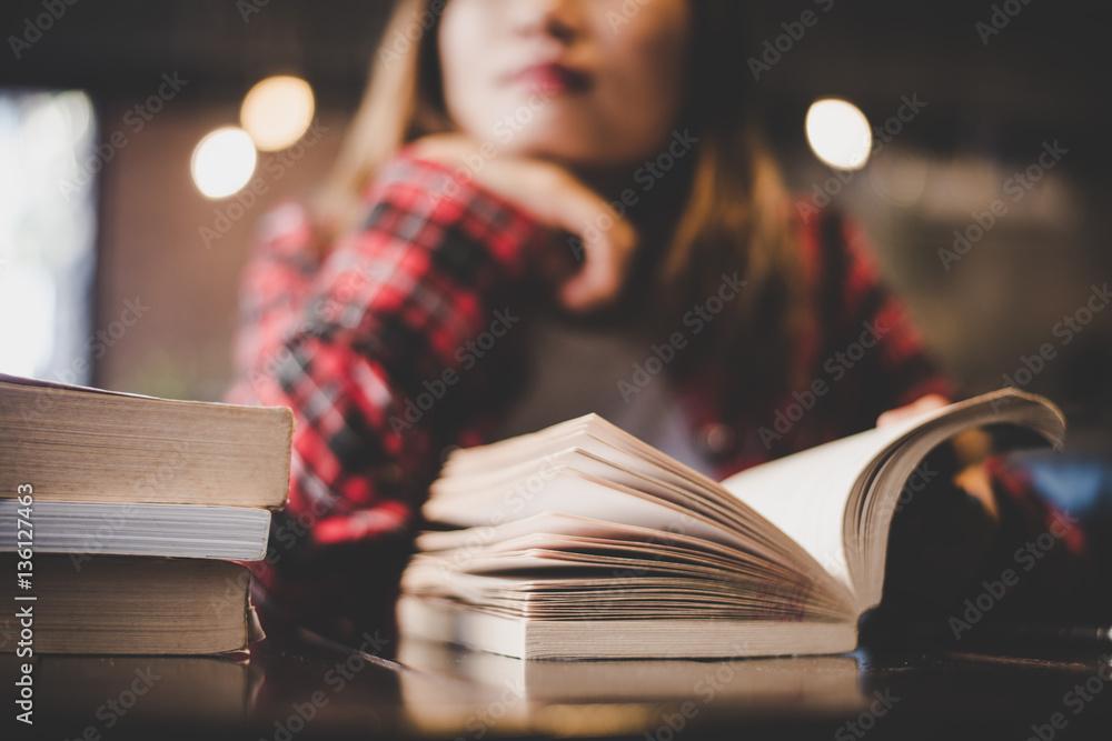 Fototapeta Hipster woman teenager sitting enjoy reading book at cafe.