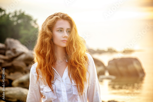 Photo Beautiful young woman with long red hair on the beach at sunset