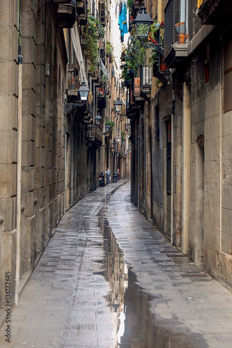 Deurstickers Smal steegje A narrow alley with puddles after a downpour in Barcelona, Spain