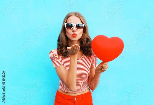 Photo  Portrait pretty woman sends air kiss with red balloon heart shap