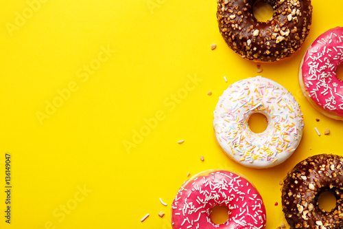 Flat lay donuts on a yellow background with copy space. Top view Poster Mural XXL