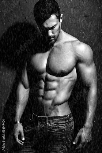 Portrait of strong healthy handsome Athletic Man Fitness Model posing near dark Canvas Print
