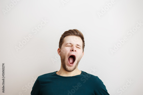 Fotografie, Obraz  Yawing  young man on a light background