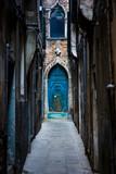 Fototapeta Uliczki - Narrow street and picturesque medieval door among old brick houses in Venice. Veneto, Italy