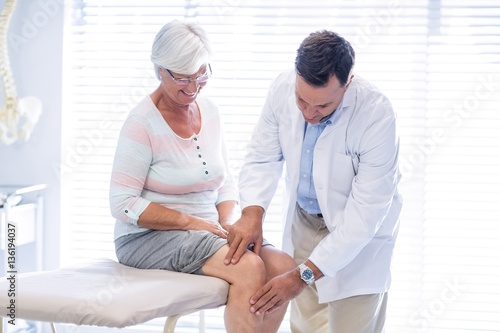 Fotografiet  Physiotherapist giving knee therapy to senior woman