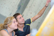 Young couple pointing upwards on climbing wall