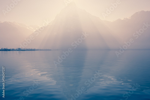 Poster Reflexion Sun rays over the top of the mountains reflected in the lake. Play of light and shadow creates volume pyramid shape in nature.