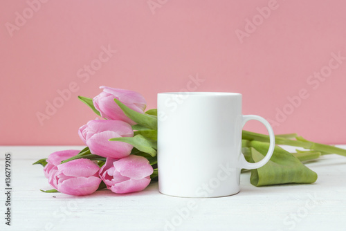 White coffee mug with pink tulips on a pink background. Space fo