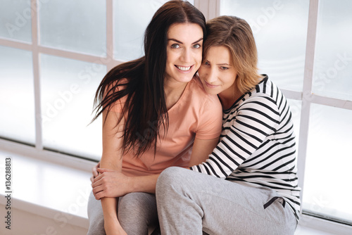 Fotografia  Cute emotional couple sitting on a window sill