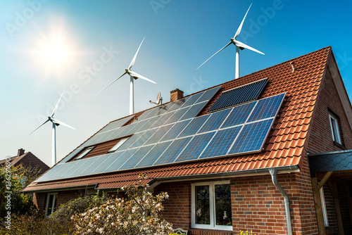 Fotografia Solar panel on a roof of a house and wind turbins arround - concept of sustainab