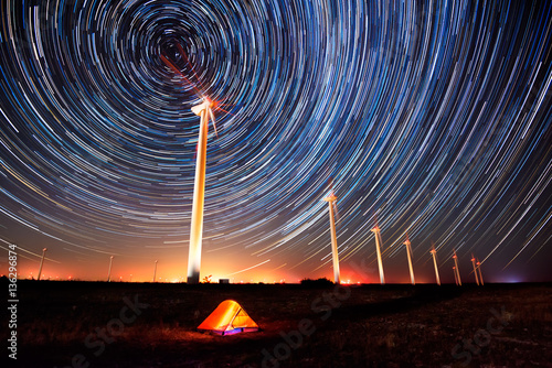 Photo Stands Black Circles in the night sky / Long time exposure night landscape with star trails over a wind farm