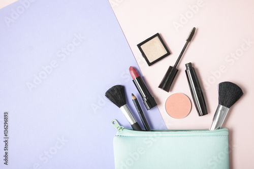 Obraz Make up products spilling out of a pastel blue cosmetics bag, on a pink and purple background with blank space at side - fototapety do salonu