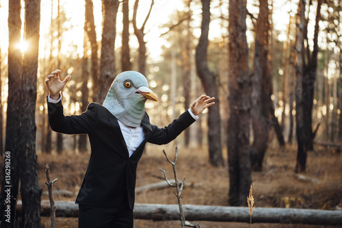 Weird businessman in a rubber bird mask pretending to fly in the sunset forest Wallpaper Mural