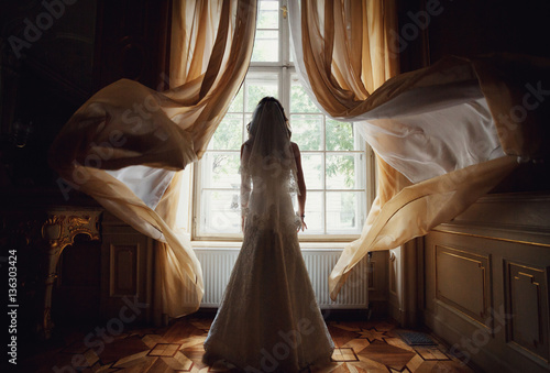 The charming bride stands near window in the restaurant Poster