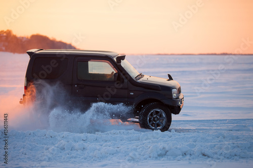 Fotomural Suzuki Jimny moving on ice of a frosn river at sunset