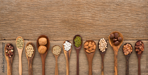 Fotografie, Obraz  Different kind of beans and lentils in wooden spoon on wood back