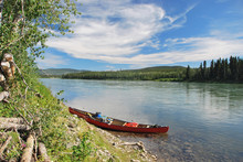 Tied Up And Abandoned Red Canoe Lying On The River Bank Of The Yukon River In Canada