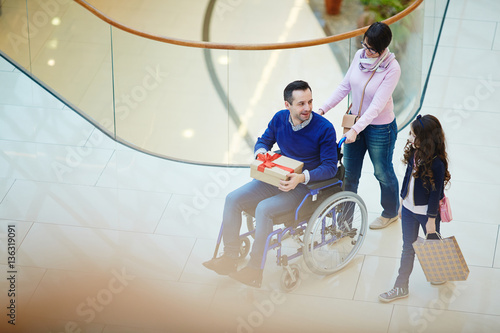 Obraz na plátně  Disabled man, his wife and daughter shopping together