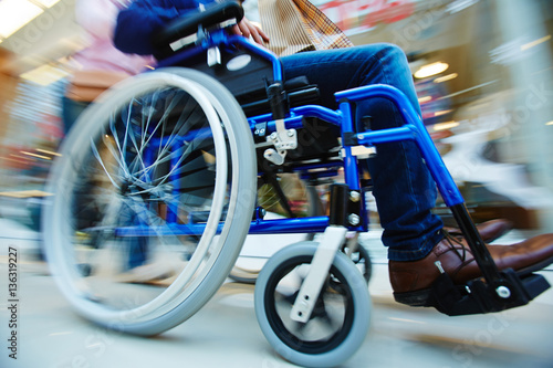 Foto  Invalid man in wheel-chair being pushed by caregiver