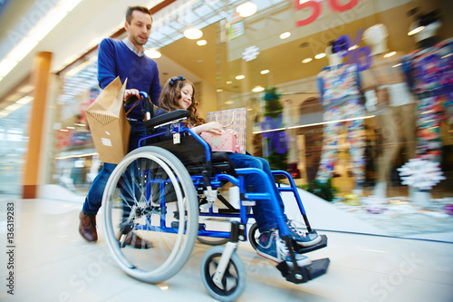 Valokuva  Man and his daughter in wheelchair shopping together during sale