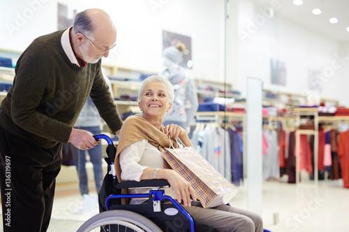 Fotografie, Obraz  Senior caregiver taking his disabled wife to go shopping