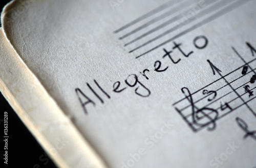 Musical tempo Allegretto in a music book with hand-written notes Wallpaper Mural