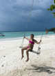 Happy little girl on swing at the beach