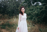 Fototapeta Las - Wedding. Young beautiful bride with hairstyle and makeup posing in white dress.Soft sunset light summer portrait. Girl looking in camera