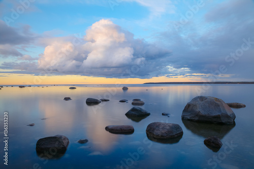 Photo sur Plexiglas Zen pierres a sable Tranquil view of sunset with stones in the water. On shore of the Baltic Sea in Estonia.