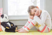 Young Girl Sitting With Soft Toy
