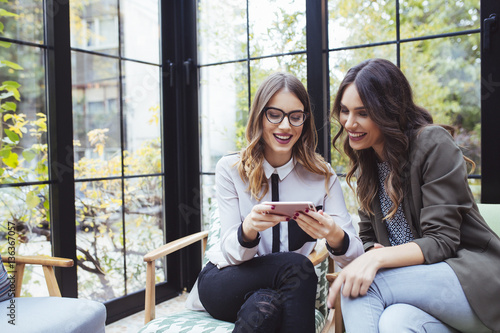 Female colleagues using mobile phone in cafe