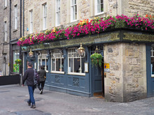 Sidewalk With Old Stone Building And British Pub Decorated With Flowers