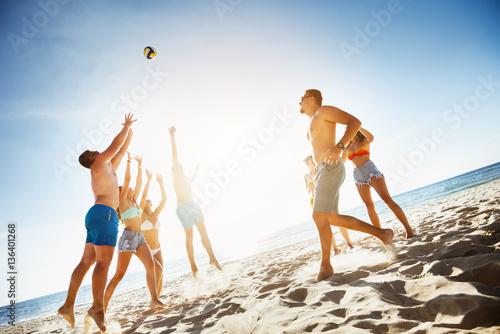 Plakat Grupowi przyjaciele bawić się piłki plażowego morze