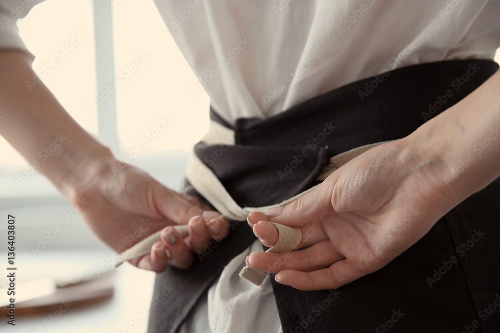 Fototapeta Woman  tying up her apron around the waist