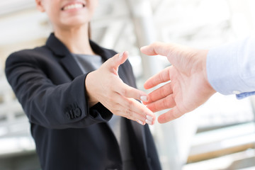 Young businesswoman going to make handshake with a businessman