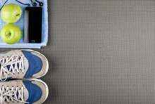 Smartphone, Headphones, Apple On Blue Towel And Sneakers On Mat