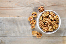 Walnuts In Bowl On Wooden Tabl...