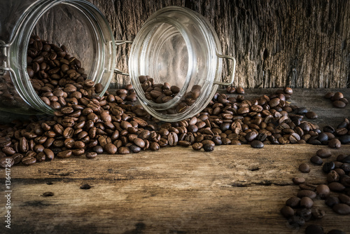 ziarnka-kawy-w-szklanym-sloiku-rozsypane-na-drewnianym-stole