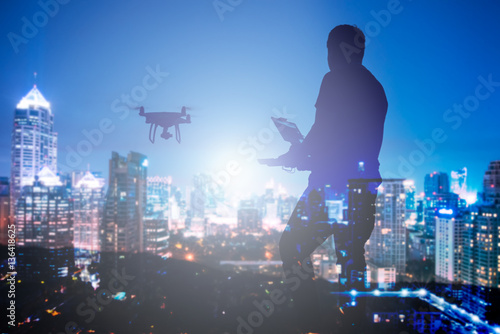 Man playing with the drone by remote control. Silhouette against the the cityscape at night background.