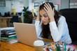 Upset female graphic designer looking at laptop