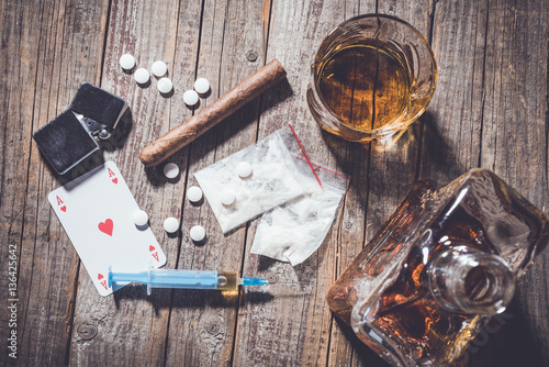 Photo Hard drugs and alcohol on an old wooden table