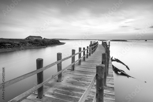 Ancient pier and abandoned boat at black and white fine art photography