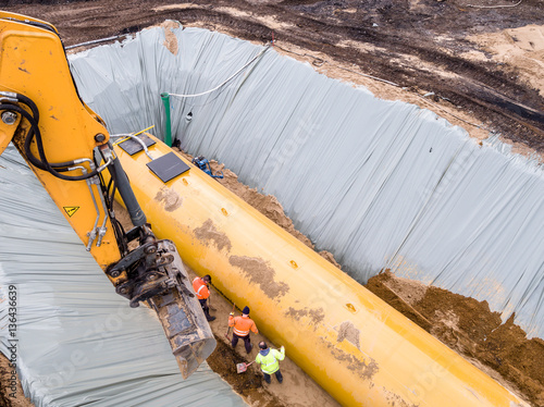 Photo  Worker installing a huge fuel tank