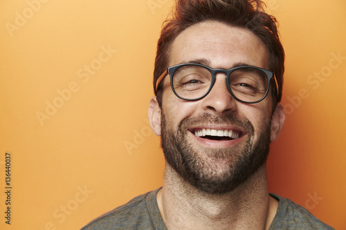Photo  Man laughing in orange studio, close up
