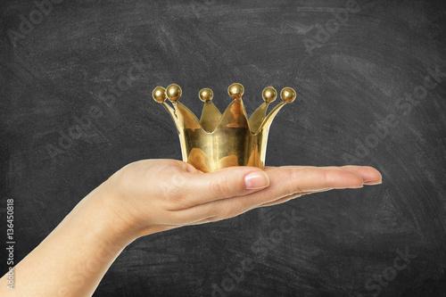 Goldene Krone auf Hand vor Schultafel Canvas-taulu