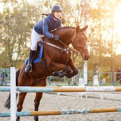 Young rider girl at show jumping. Horserider jumps over hurdle
