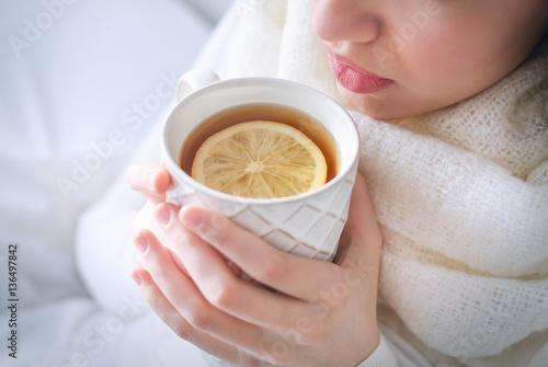 Photo sur Toile The Young ill woman drinking hot tea with lemon at home, closeup