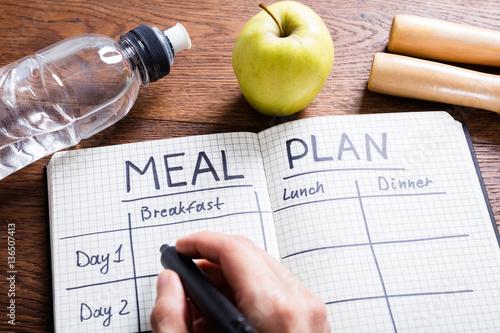 Foto op Canvas Kruidenierswinkel Person Hand Filling Meal Plan In Notebook